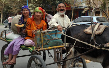 family riding on a donkey cart returns from a bazaar in Hotan