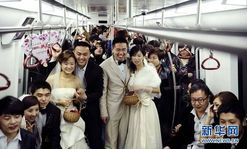 Newlyweds pose for a photo in a subway carriage in Shenyang, capital city of northeastern China's Liaoning Province on April 19, 2011. Eight couples held a group wedding in the subway with the trains full of people bearing witness to their love. [Xinhua]