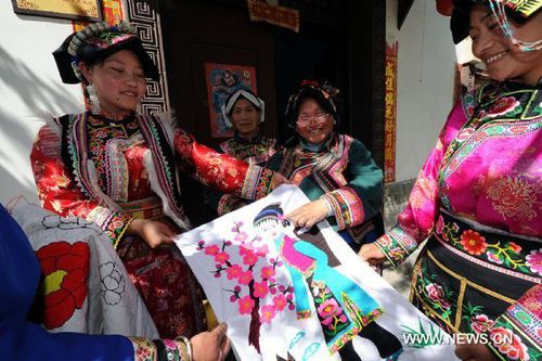 An aged woman of the Qiang ethnic group explains embroidery skills in Muka Village of Lixian County, southwest China's Sichuan Province, April 15, 2011. The embroidery of the Qiang ethnic group has been listed as one of the national intangible cultural heritages. [Xinhua/He Junchang]