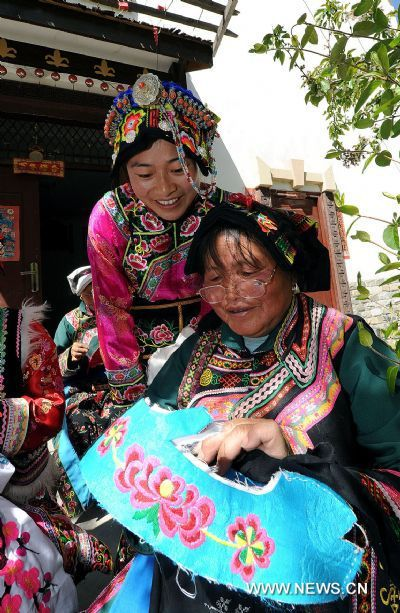 An aged woman of the Qiang ethnic group instructs embroidery skills in Muka Village of Lixian County, southwest China's Sichuan Province, April 15, 2011. The embroidery of the Qiang ethnic group has been listed as one of the national intangible cultural heritages. [Xinhua/He Junchang]