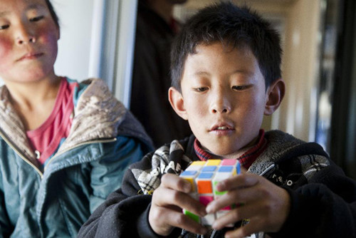 A child plays a Rubik's cube at a train that runs on the Qinghai-Tibet railway in southwest China's Qinghai Province, Jan. 29, 2012. The Qinghai-Tibet Railway Company carried out 20 new services as the number of passengers rises after the Spring Festival holiday. The new services includes providing poker cards, chess, toys and so on for passengers. [Xinhua/Wu Gang]