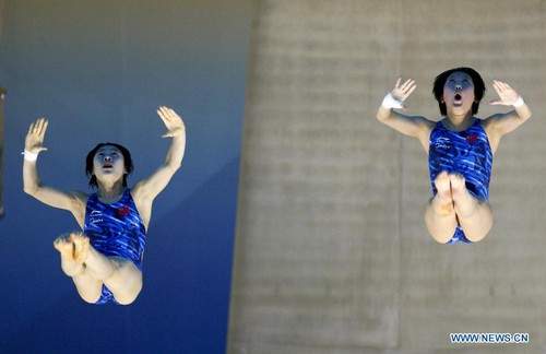 Chen Ruolin (L) and Wang Hao of China compete during the women's synchronized 10m platform final at the FINA Diving World Cup, a London 2012 Olympics test event, at the Olympic Aquatics Center in London, Britain, on Feb. 22, 2012. Chen and Wang won the title with 359.58 points. [Xinhua]