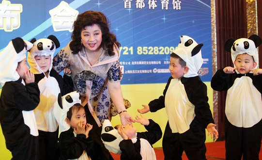 Hong Kong singer Paula Tsui posing for a photo with the children dressed up as pandas. [qq.com]