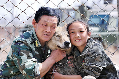 Zhu Yongsheng and his daughter Zhu Lin cuddle a wolf at the family's animal training base in Urumqi, the Xinjiang Uygur autonomous region, on April 8, 2012. [China Daily]