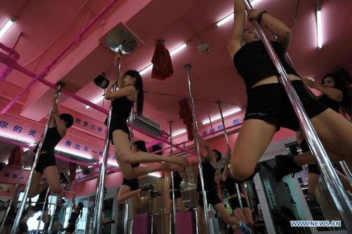 Girls pole dance at a fitness center in Hefei, capital of east China's Anhui Province, on August 25, 2012. More and more Chinese people have taken up pole dancing as a fun way to keep healthy. [Xinhua]