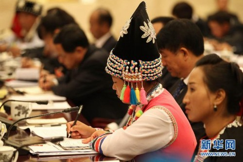 A delegate wearing a traditional ethnic minority costume takes notes at the panel discussion of delegates from southwest China's Yunnan Province on November 9, 2012, during the 18th CPC National Congress. [Xinhua]