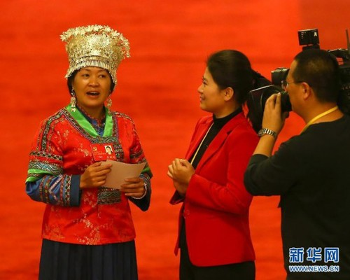 Delegate to the 18th CPC National Congress and primary school teacher from southern China's Hunan Province Chao Hong (L) wears her Miao ethnic minority costume. She sings a local folk song during an interview on November 9, 2012. [Xinhua]