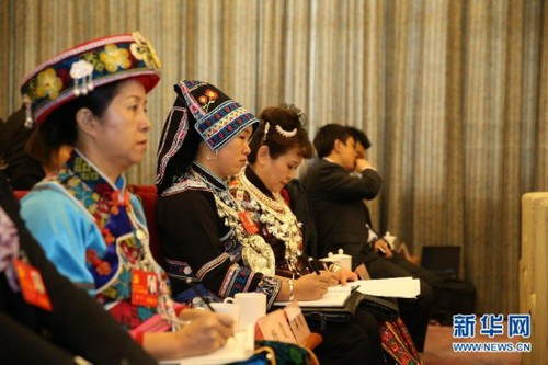 During the 18th CPC National Congress, delegates wearing traditional ethnic minority costumes attend the panel discussion of delegates from southwest China's Guizhou Province on November 10, 2012. [Xinhua]
