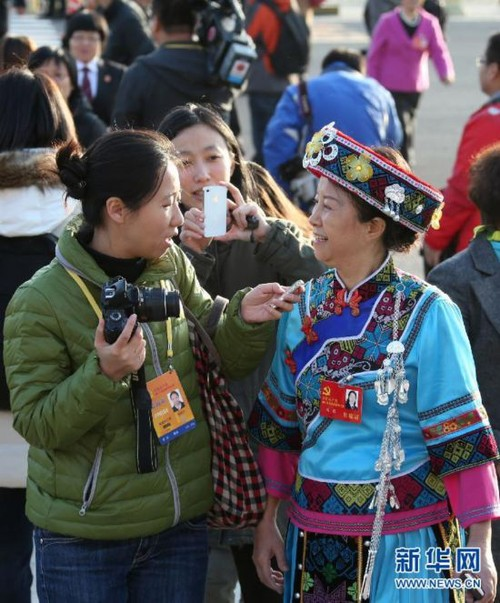 Delegate to the 18th CPC National Congress and judge from Tongchuan Intermediate People's Court in southwest China's Guizhou Province Yang Xia (R) wears her ethnic minority costume while giving an interview at Tian'anmen Square on November 8, 2012. [Xinhua]
