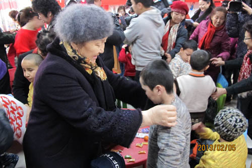 Volunteer mothers help the children put on the sweaters. [Xinjiang Women's Federation/Sui Jian]