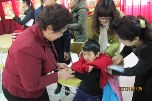 Volunteers and staff members help a boy put on his sweater. [Xinjiang Women's Federation/Sui Jian]