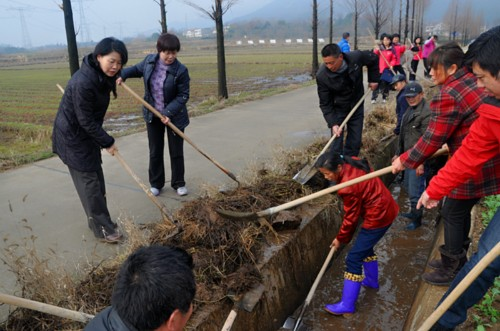 President of Hubei Women's Federation Xiao Juhua (L) and local villagers clean ditches in Duhe Village in central China's Hubei Province on February 1, 2013. [Women of China / Zhu Fen]