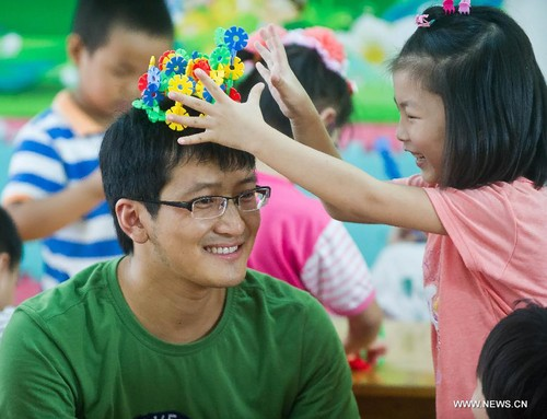 A girl places a handmade 'crown' on her teacher, Wang Yu, at a kindergarten in Tongxiang, east China's Zhejiang Province. Wang is the first male kindergarten teacher in Tongxiang. [Xinhua]