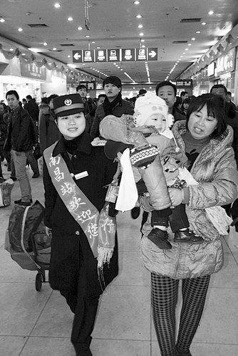 Li Jun (L) helps a woman passenger with a baby push her luggage. [yzdsb.com.cn]