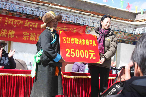 Farming tools are presented to local residents by Tibetan Women's Federation in Changlong Village in Gangba County, western China's Tibet Autonomous Region [Tibetan Women's Federation / Zhang Hongping]