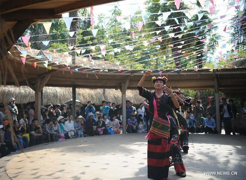 Visitors watch traditional performance of Wa ethnic group at Ethnic Villages in Kunming, capital of southwest China's Yunnan Province, April 4, 2013, the first day of the three-day Qingming Festival holidays. [Xinhua]