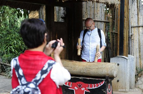 A foreign visitor plays a traditional drum of Wa ethnic group at Ethnic Villages in Kunming, capital of southwest China's Yunnan Province, April 4, 2013, the first day of the three-day Qingming Festival holidays. [Xinhua]