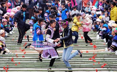 "Tourists play with local residents during a folk custom and culture festival marking the ""San Yue San"" (the third day of the third lunar month in Chinese Calendar) in Shizong County, southwest China's Yunnan Province, April 12, 2013. The festival, attracting tens of thousands of local residents and tourists from both at home and abroad, was held here Friday. [Xinhua]"