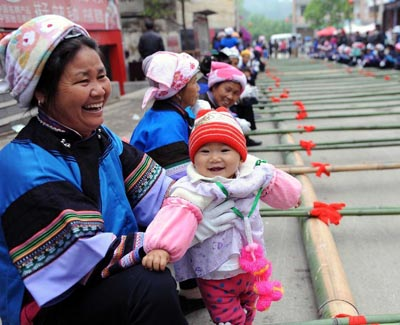 "A woman of Dai ethnic group watches the performance with her grandson during a folk custom and culture festival marking the ""San Yue San"" (the third day of the third lunar month in Chinese Calendar) in Shizong County, southwest China's Yunnan Province, April 12, 2013. The festival, attracting tens of thousands of local residents and tourists from both at home and abroad, was held here Friday. [Xinhua]"