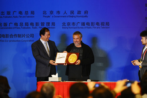 Luc Besson (right) shows off his autographed clay handprint. [Women of China/Zhang Jiamin]