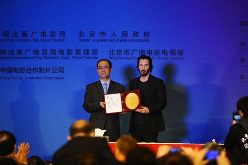 Keanu Reeves (right) shows off his autographed clay handprint. [Women of China/Zhang Jiamin]