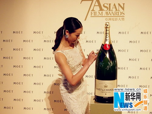 Qi Xi autographs a bottle of champagne at the 7th Asian Film Awards. [Xinhua]