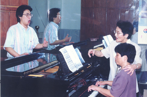 Zhou (Right, back) teaches Liao Yongchang (L) to sing in class. [shcmusic.edu.cn]