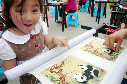 A child admires a Shu embroidery work at the Anjing International Embroidery Festival in Sichuan province on Sunday. [China Daily/Wang Jun]