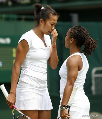Megan Moulton-Levy (R) of the United States and Zhang Shuai of China talk to each other during the first round of ladies' doubles against Mona Barthel of Germany and Liga Dekmeijere of Latvija on day 3 of the Wimbledon Lawn Tennis Championships at the All England Lawn Tennis and Croquet Club in London, Britain on June 26, 2013. Moulton-Levy and Zhang won 2-1. [Xinhua]