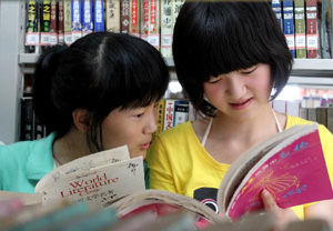 Children read books at the library in Fanchang County, east China's Anhui Province, June 26, 2010. A free reading room collecting nearly 10,000 books was set at the library of Fanchang for children to enrich their summer vacation. [Xinhua/Yang Hua]