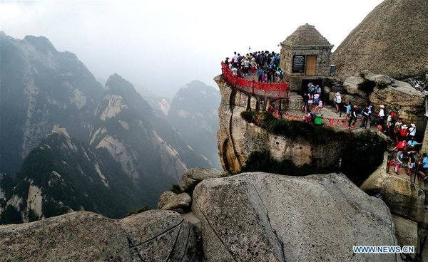 Tourists Walk on Plank Road Built on Cliff at Huashan Mountain in NW China